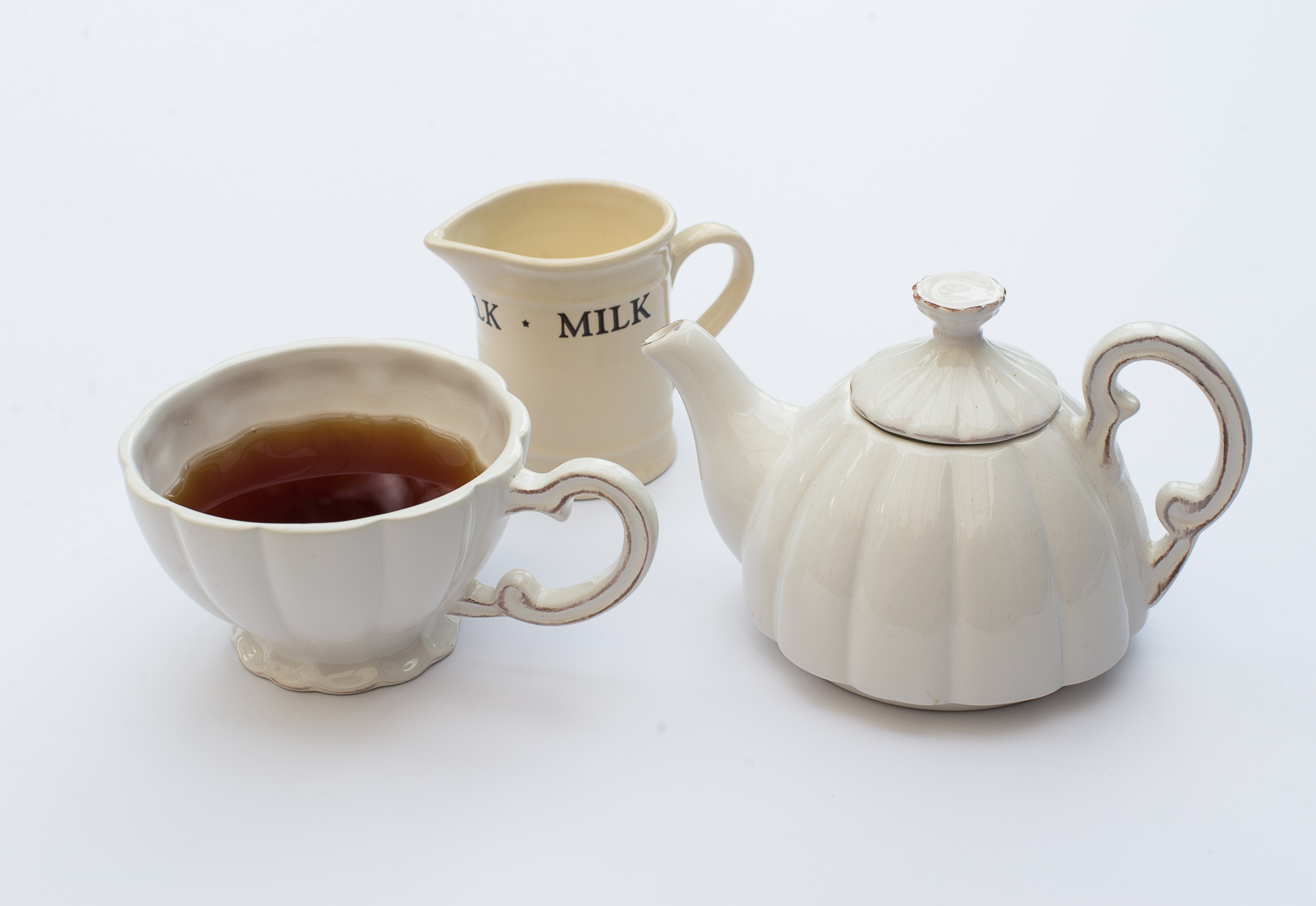 A cup of black tea with milk jug and tea pot by www.englishcreamtea.com